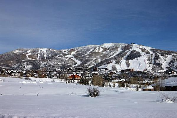 Snow covered mountains rise in the distance over Steamboat Springs, Colorado.