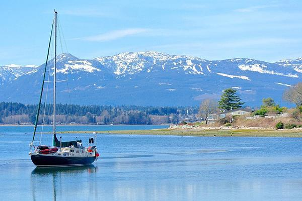 A boat glides on the waters of Comox in front of a backdrop of mountains in British Columbia