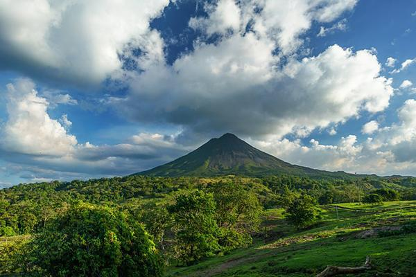 A volcano surrounded by lush greenery rises up to the sky in Costa Rica