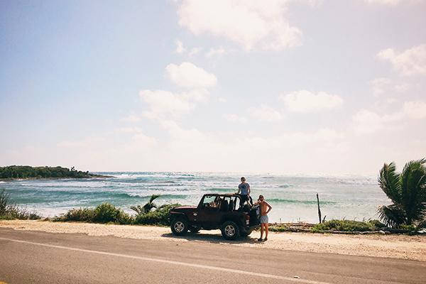 Travellers stop in their jeep on the side of the road to admire the ocean in Cozumel, Mexico