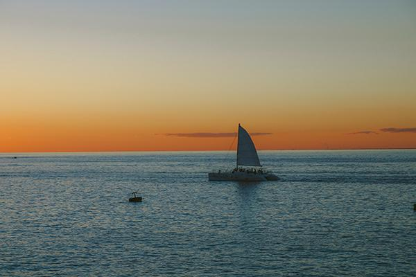 A sailboat glides across the water as the sun sets in Cozumel, Mexico