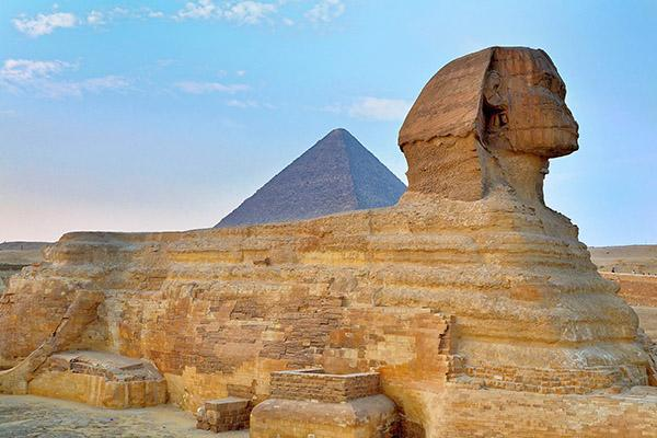 The Great Sphinx sits proudly in front of a pyramid in Giza, Egypt