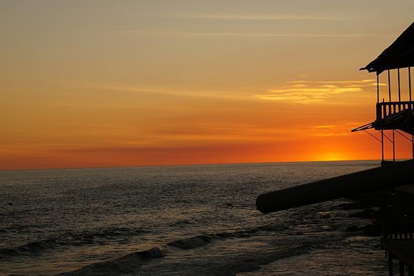 A sunset kisses the ocean on the coast of El Salvador