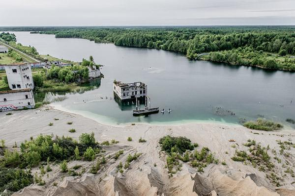Paddleboarders explore ruins that lie in the shallow waters of Rummu, Estonia