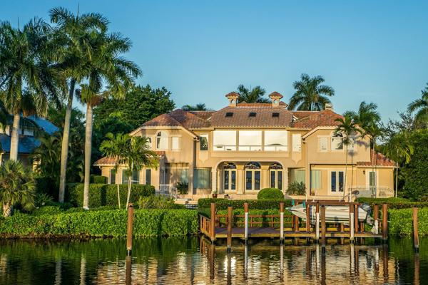 A mansion sits proudly on the shores of a canal in Naples, Florida