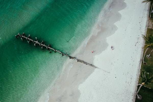 Aerial view of a derelict dock on a beach in Naples, Florida