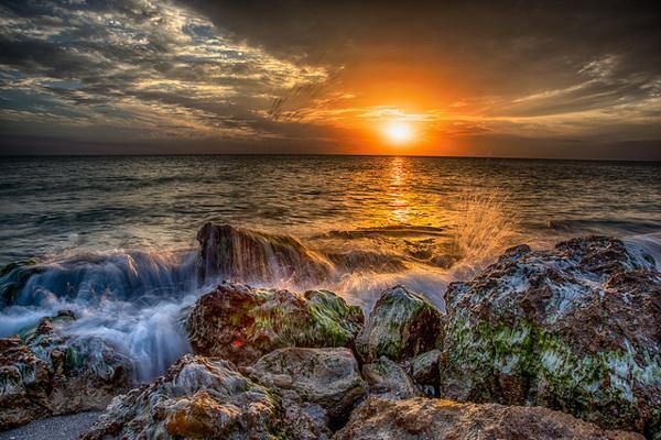 Waves crash onto the rocky shore at Caspersen Beach in Venice, Florida