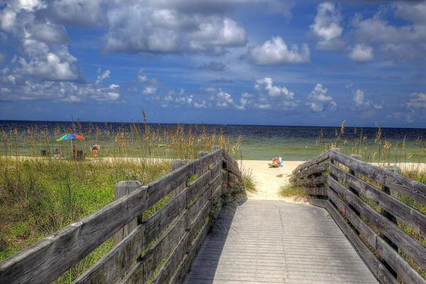A wooden path leads to a tranquil beach in Venice, Florida