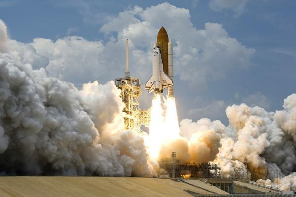 The engines fire on a space shuttle propelling it into the atmosphere from Cape