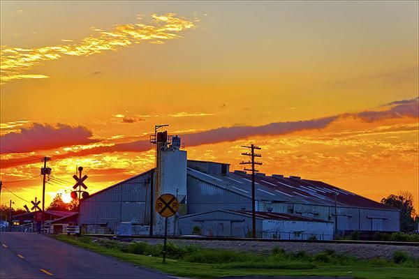 The setting sun sets fire to the sky behind an industrial building and train tracks in Fort Smith, Arkansas