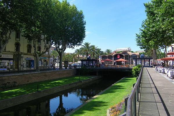 Canals and lush green trees characterise the streets of Perpignan, France
