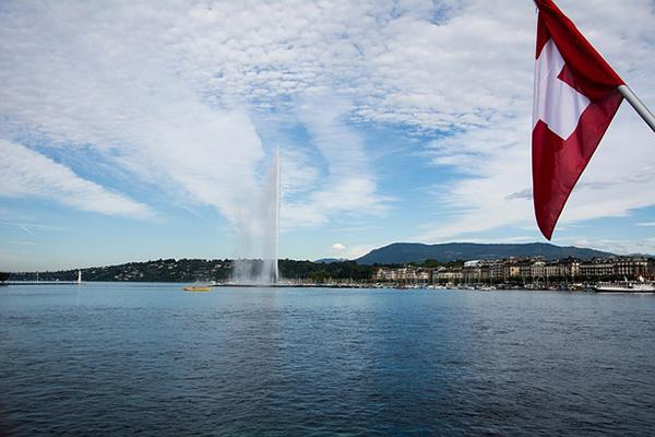 The Jet d'Eau fountain on Lake Geneva, with a Swiss flag in the foreground