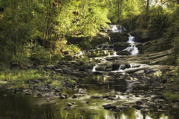 A small waterfall cascades down rocks in Augusta, Georgia