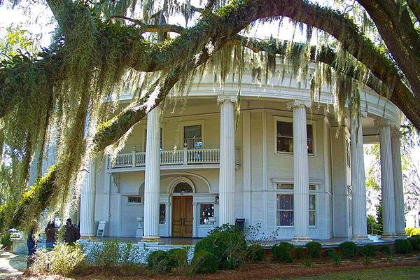 The Crescent mansion stands in the shade of giant trees in Valdosta, Georgia