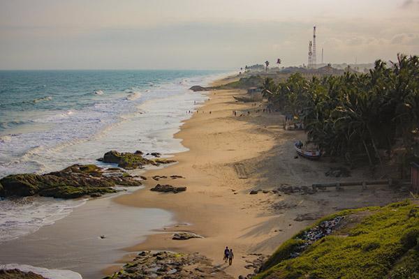 Beachgoers walk along the sand at Cape Coast, Ghana