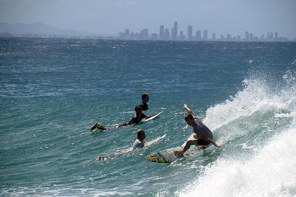 A group of surfers take on Gold Coast waves with the city skyline in the distance