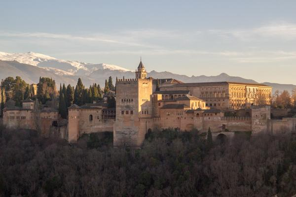 The Alhambra fortress stands proudly in the foothills of the Sierra Nevada mountains in Granada, Spain