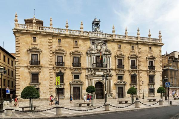 Tourists pass by an historic courthouse in Granada, Spain