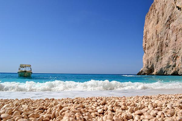 A turquoise blue wave crashes to the shore of a beach in Zakynthos, Greece