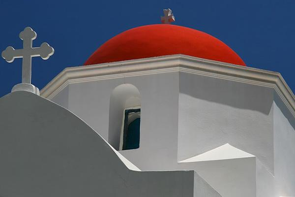 Crosses and a bright red dome top a church in Karpathos, Greece
