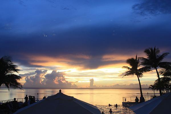 Beachgoers enjoy the splendours of a tropical sunset in Guam, Micronesia