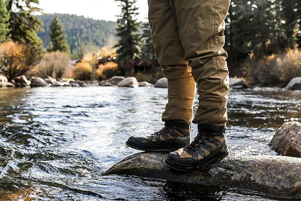 A fly fisherman stands on the river rocks in the beautiful surrounds of Gunnison, Colorado