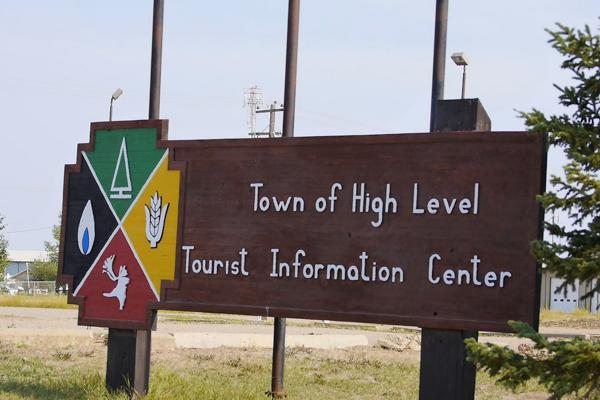 A local sign pointing to information services for the town of High Level, Canada
