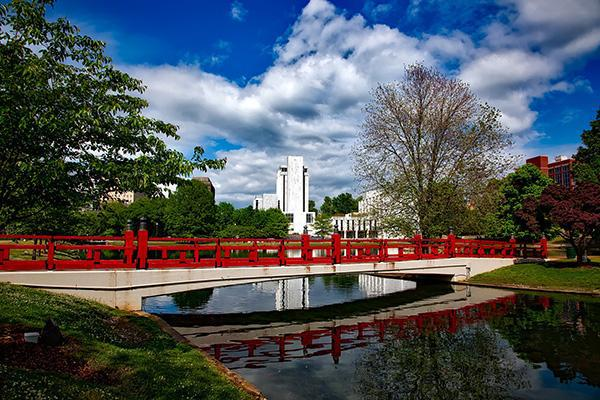A red bridge sits over a small river in Huntsville, Alabama