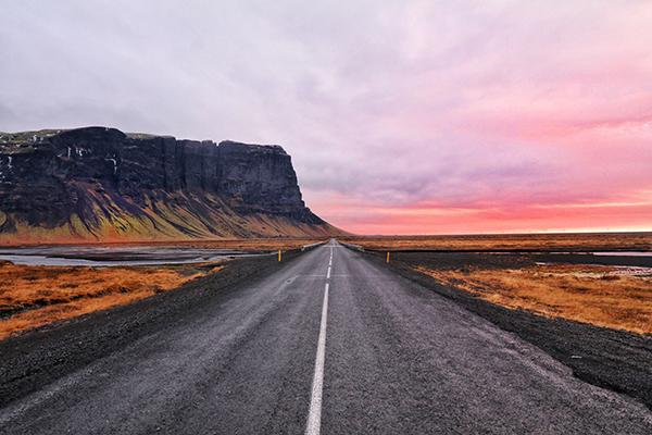 An open, Icelandic road with mountains on one side and a stunning sunset on the other