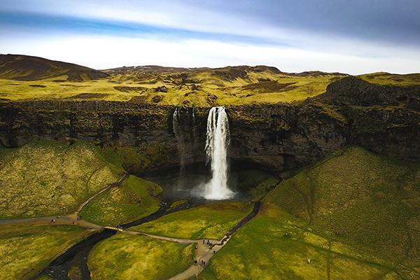 The Seljalandsfoss Waterfall surrounded by the lush and vibrant landscape of Iceland