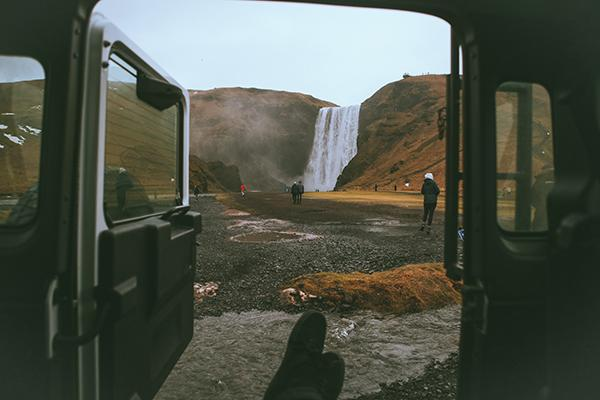 A traveller sits inside a 4WD vehicle admiring a beautiful waterfall in Iceland