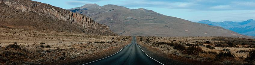 An empty road leads towards the mountains of Patagonia, Argentina