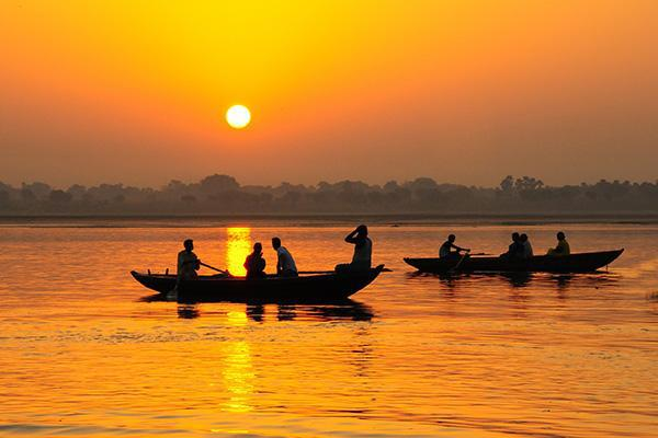 People in boats on the Ganges River as the sun sets