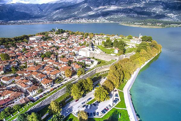 Birds-eye view of houses, hills and a lake in picturesque Ioannina, Greece