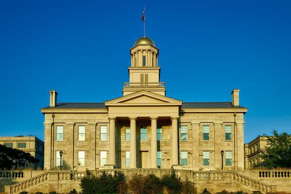 The old State Capitol building stands proudly under a bright blue sky in Iowa City, Iowa