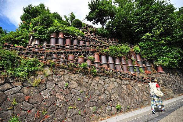 A woman walks past a path of copper pipes in Ishigaki, Japan