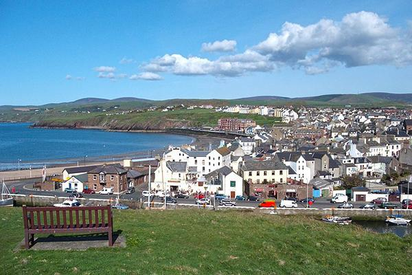 A pretty little village sits next to the sea on the Isle of Man on the waters between Ireland and the United Kingdom