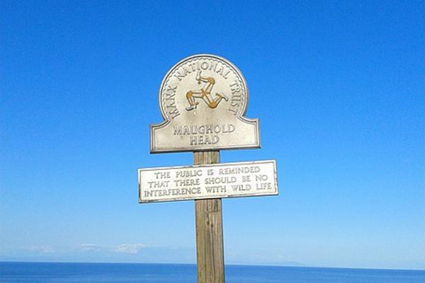 A sign in front of the sea with the Coat of Arms of the Isle of Man (Maughold Head) (Manx National Trust)