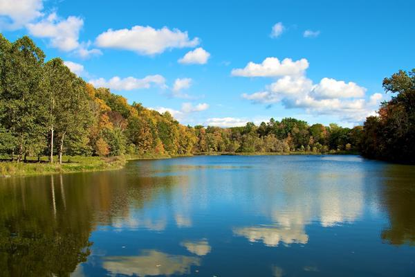 The fall colours reflect off the lake outside of Ithaca, New York