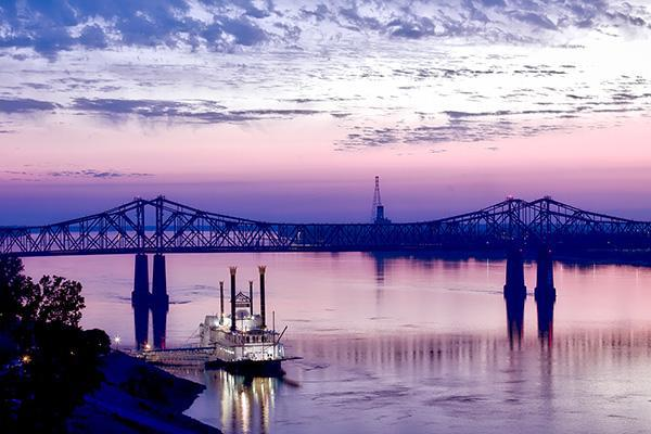 View a bridge over the Mississippi River at dusk from Natchez, Mississippi