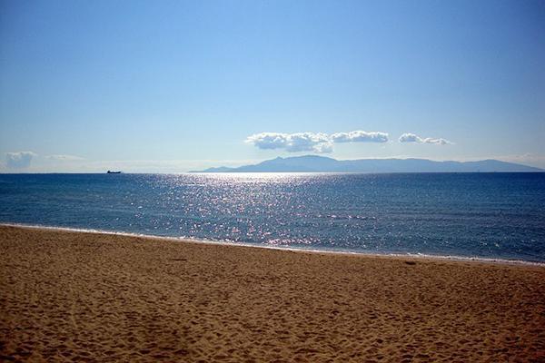 A golden sand beach next to a sparkling sea in Kavala, Greece