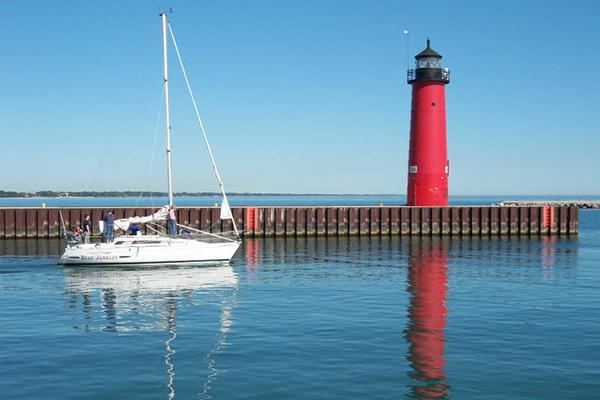 A small sailboat glides next to the Kenosha North Pier Lighthouse in Kenosha, Wisconsin