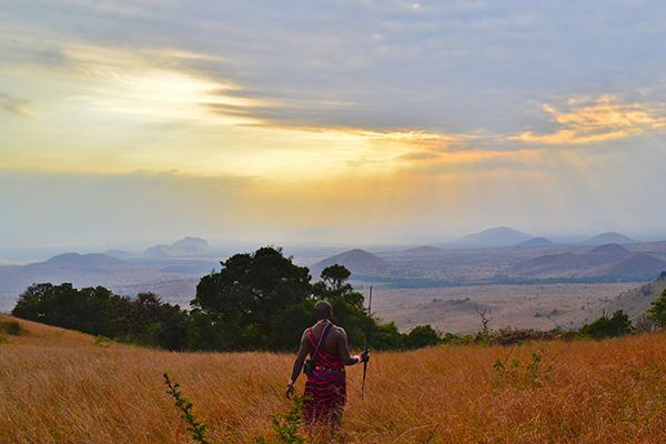 A Masai warrior stands in the Chyulu Hills as the sun washes its light across the beautiful landscape