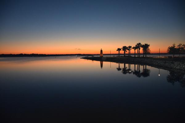 The sun sets over the famous lighthouse at the end of a pier on Lake Toho in Kissimmee, Florida