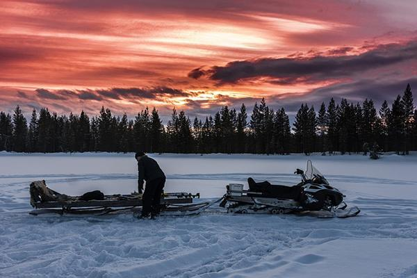 A snowmobiler checks their gear at sunrise in Lapland