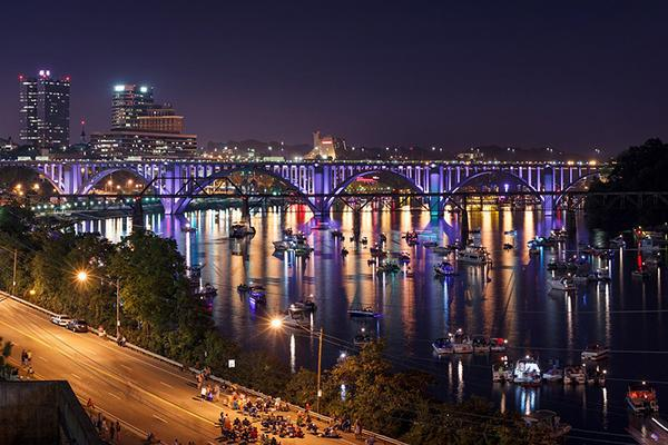 The city lights of Knoxville Tennessee shining brightly over the water