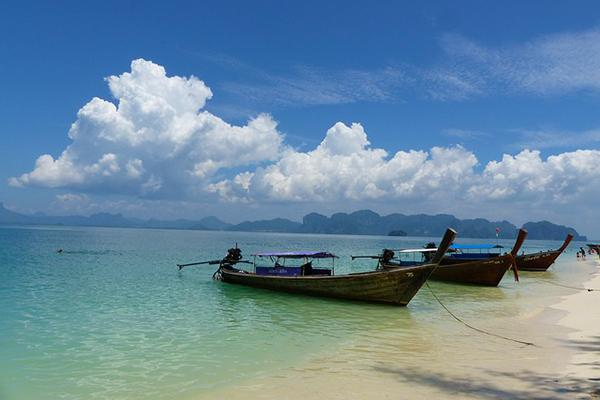 Longboats line the beach on a beautiful day in Krabi, Thailand