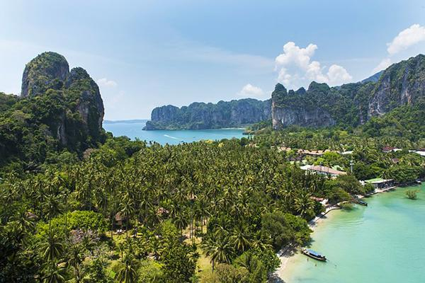 Tropical trees and dramatic cliffs decorate the surrounds of Railay Bay's beaches in Krabi, Thailand