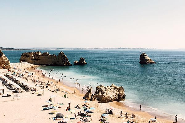 Sunseekers crowd a stunning beach in Lagos, Portugal