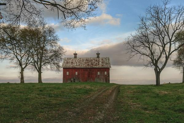 A red farmhouse perched at the top of a hill near Lancaster, Pennsylvania